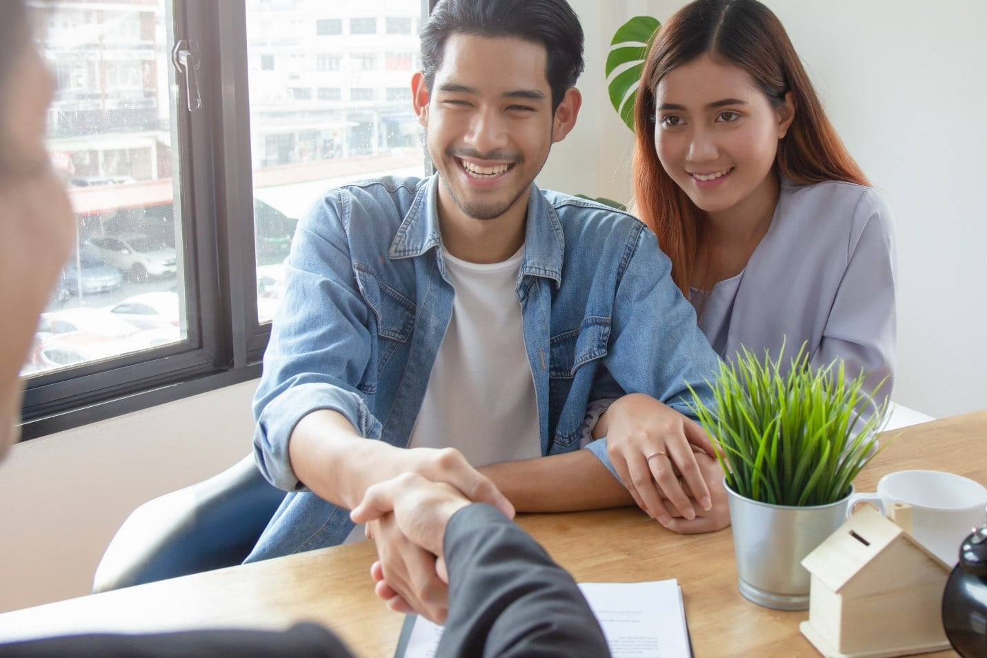 Man and woman shaking hands with property manager