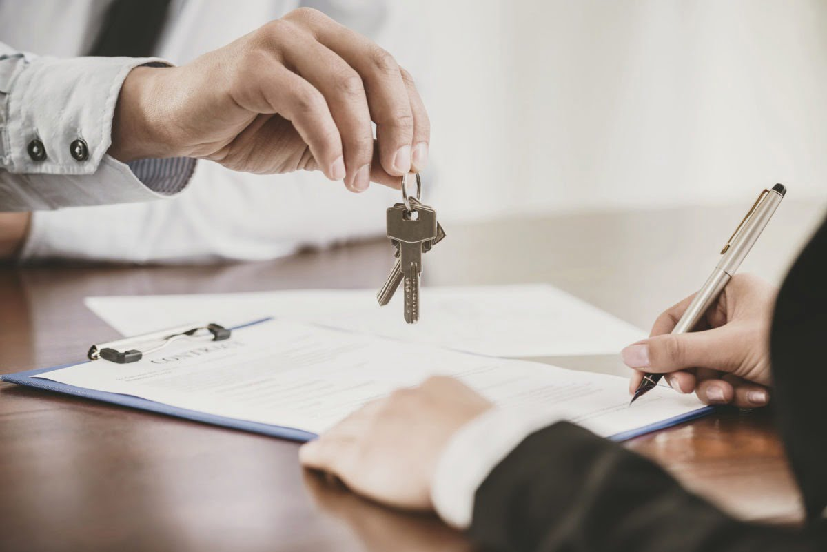 A person signs a lease and gets rental keys
